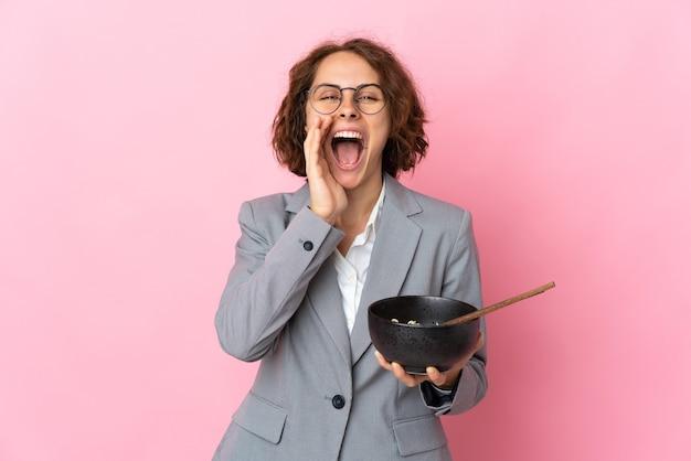 Jeune femme anglaise sur rose criant avec la bouche grande ouverte tout en tenant un bol de nouilles avec des baguettes