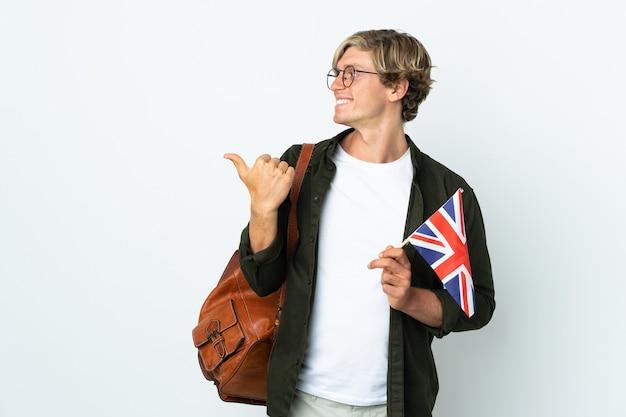 Jeune femme anglaise tenant un drapeau du royaume-uni pointant sur le côté pour présenter un produit