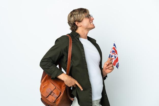Jeune femme anglaise tenant un drapeau du royaume-uni souffrant de maux de dos