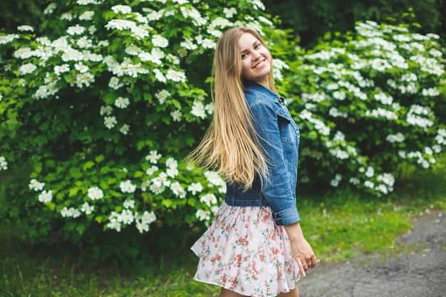 Une jeune femme d'apparence européenne aux longs cheveux blonds, vêtue d'une robe courte, se dresse sur fond de buissons à fleurs blanches. journée de printemps ensoleillée. beauté féminine naturelle