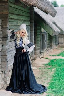 Une jeune femme d'apparence slave avec couronne, kokoshnik au milieu de l'été, village, ferme