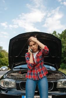 Jeune femme appelant une dépanneuse sur route, panne de voiture. voiture cassée ou accident d'urgence avec un véhicule, problème de moteur sur autoroute