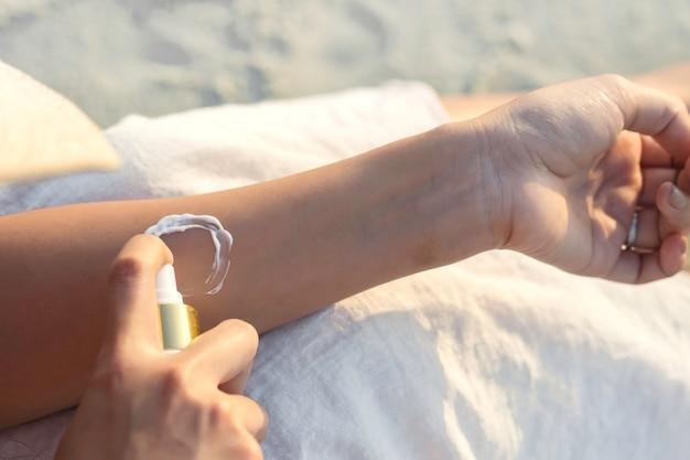 Jeune femme, application, crème écran solaire, main, tenue, bouteille crème solaire, protection solaire