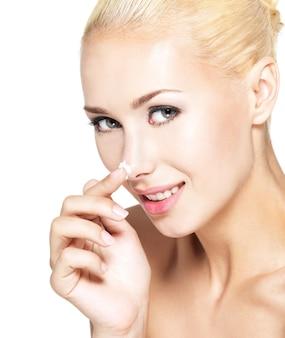 Jeune femme appliquant une crème cosmétique sur le nez - isolé