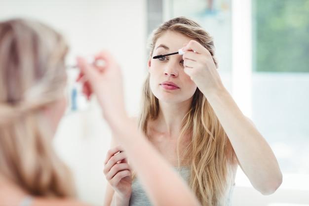 Jeune femme appliquant du mascara