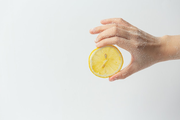 Jeune femme appliquant un gommage au citron naturel sur les mains contre une surface blanche