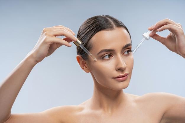 Jeune femme appliquant de l'huile cosmétique sur la peau
