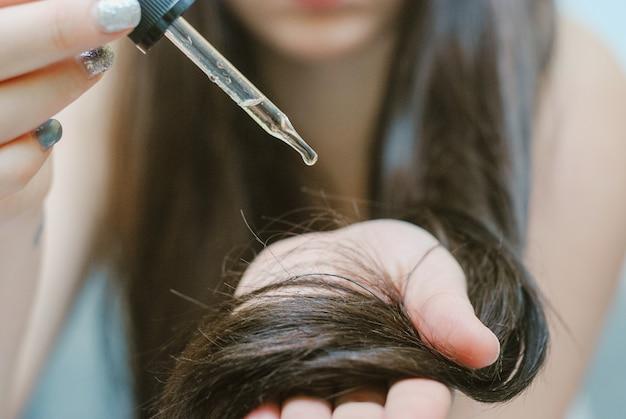 Jeune femme appliquant de l'huile sur ses cheveux, à l'intérieur