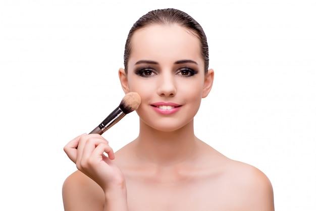 Jeune femme appliquant maquillage isolé sur blanc