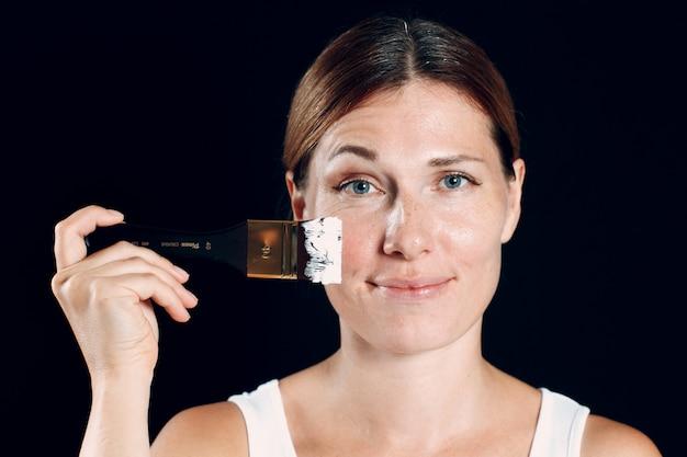 Jeune femme appliquant le maquillage, peint le visage avec le pinceau et le maquillage. comment ne pas faire de concept de maquillage.