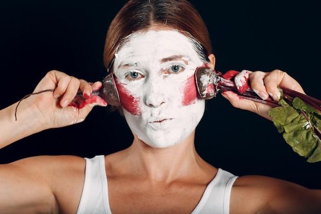 Jeune femme appliquant le maquillage, les peintures rougissent le visage avec la betterave et le maquillage. comment ne pas faire de concept de maquillage.