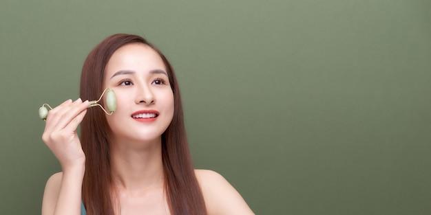 Jeune femme appliquant un massage du visage au rouleau de jade