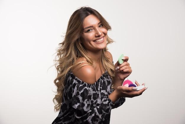 Jeune femme appliquant la poudre heureusement sur le mur blanc.