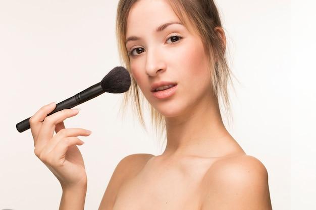 Jeune femme appliquant de la poudre sur son visage