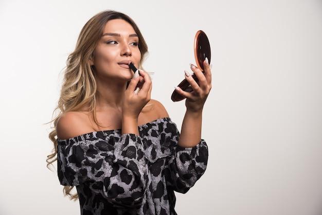 Jeune femme appliquant le rouge à lèvres sur le mur blanc.