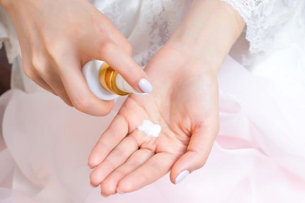 Une jeune femme applique une crème pour les mains à partir d'un tube de crème. belles mains soignées et paume à la crème. fermer
