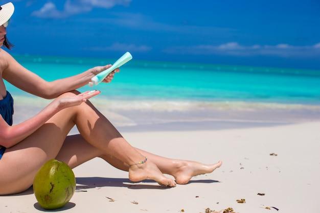 Jeune femme applique la crème sur ses jambes lisses bronzées à la plage tropicale