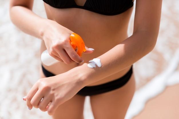 Jeune femme applique une crème solaire protectrice sur sa main à la plage.