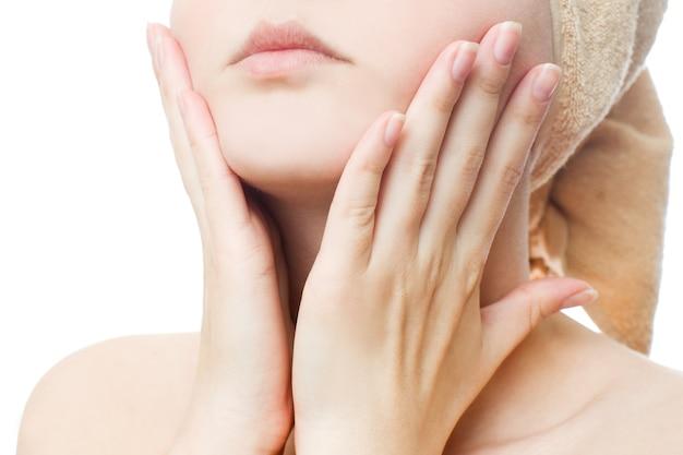 Jeune femme applique la crème sur le visage