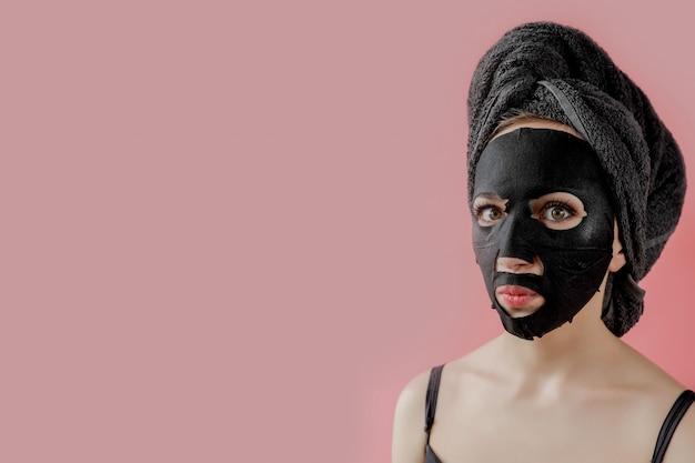 Jeune femme appliquer un masque facial en tissu cosmétique noir sur fond rose. masque peeling visage au charbon de bois, soins de beauté spa, soins de la peau, cosmétologie. fermer