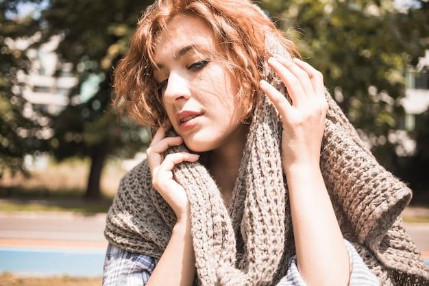 Jeune femme appréciant la douceur de l'écharpe dans le parc