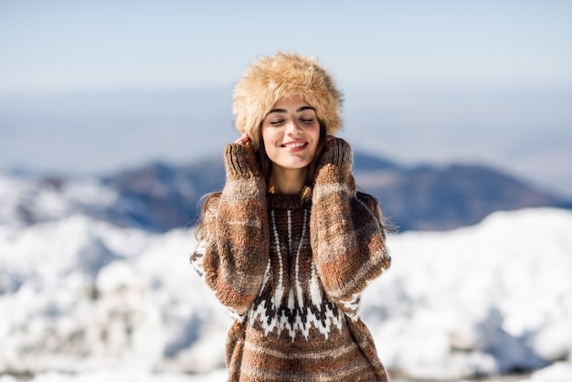Jeune femme appréciant les montagnes enneigées en hiver