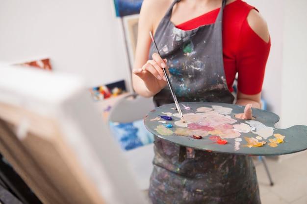 Jeune femme appréciant la peinture dans son studio d'art