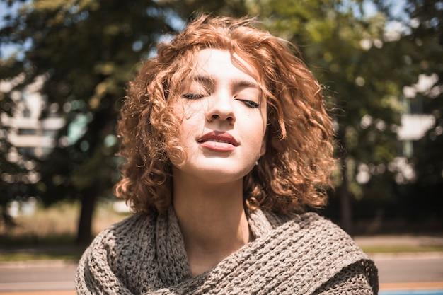 Jeune femme appréciant le vent dans le parc