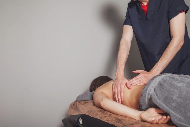 La jeune femme apprécie le massage de bien-être sportif dans le cabinet médical de la salle de fitness. massothérapeute professionnel à domicile fait des exercices de massage. concept de détente, beauté, santé, soins du corps. espace de copie