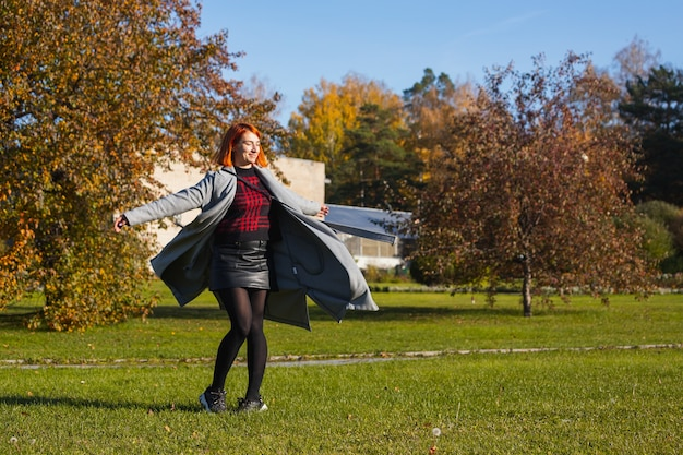 Jeune femme apprécie le soleil chaud et tourbillonne dans un parc de la ville