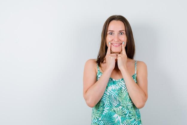 Jeune femme en appuyant les doigts sur les joues en blouse et à la gaieté. vue de face.