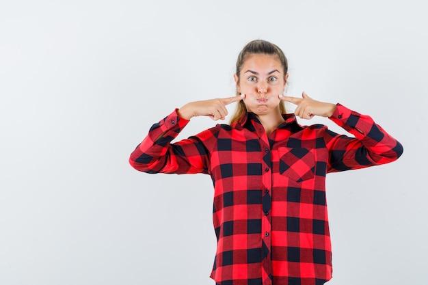 Jeune femme en appuyant sur les doigts sur les joues soufflées en chemise à carreaux et à la drôle