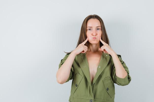 Jeune femme en appuyant sur les doigts sur les joues soufflées en veste verte