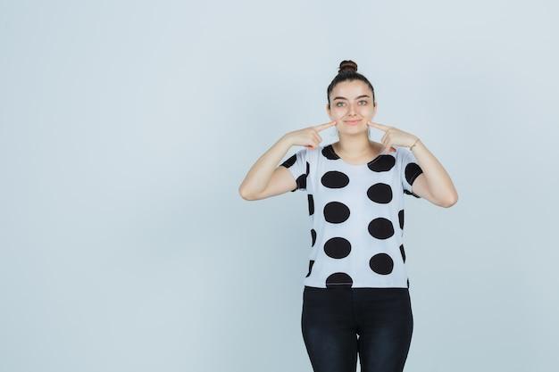 Jeune femme en appuyant sur les joues avec les doigts en t-shirt, jeans et à la jolie vue de face.