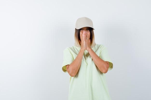 Jeune femme en appuyant sur les mains ensemble sur le visage en t-shirt, casquette et à la nostalgie. vue de face.