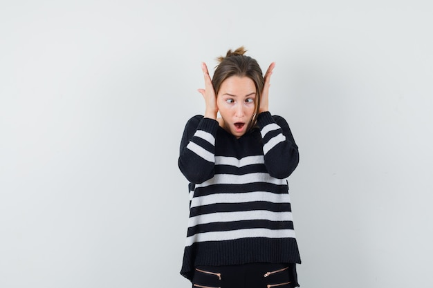 Jeune femme en appuyant sur les mains sur les oreilles en maille rayée et pantalon noir et à choqué