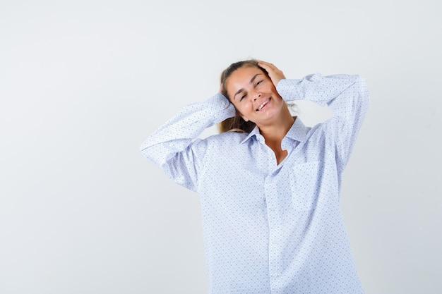 Jeune femme en appuyant sur les mains sur les oreilles, souriant en chemise blanche et à la recherche de plaisir