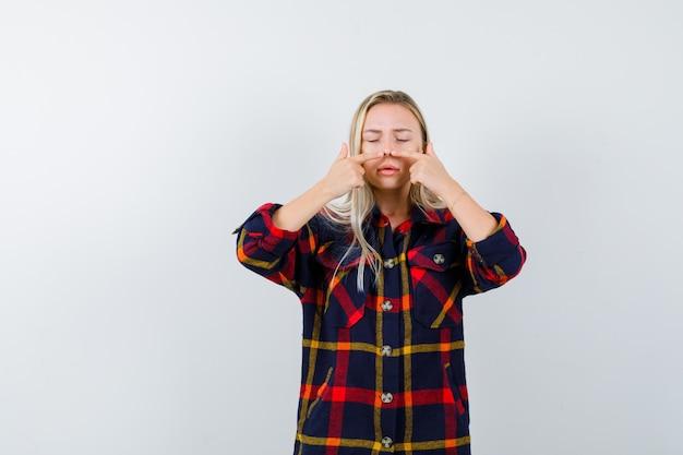 Jeune femme en appuyant sur le nez avec les doigts en chemise à carreaux et à la vue de face, focalisée.