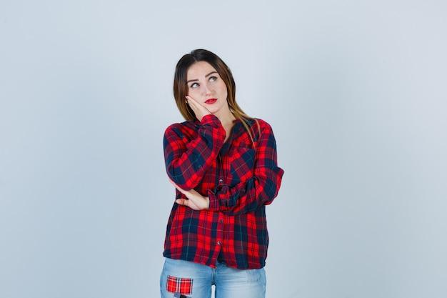 Jeune femme appuyée sur la joue de la paume, pensant à quelque chose en chemise à carreaux, jeans et regardant pensive, vue de face.