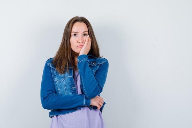Jeune femme appuyée sur la joue de la paume, regardant loin dans une veste en jean et regardant pensive, vue de face.