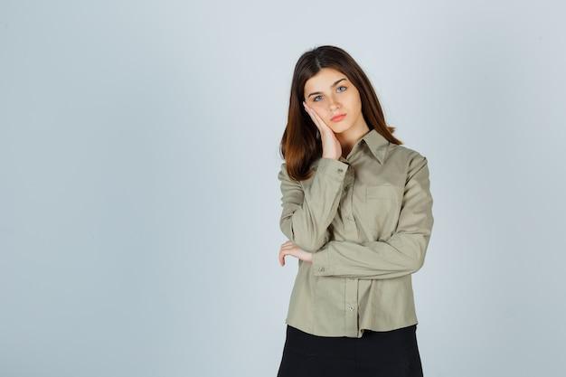 Jeune femme appuyée sur la joue de la paume surélevée en chemise, jupe et l'air triste. vue de face.