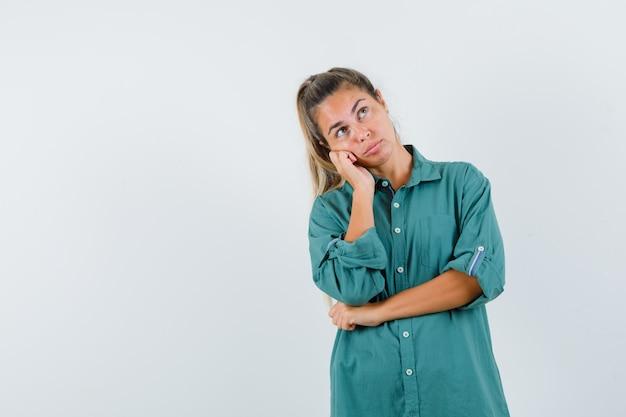 Jeune femme appuyée sur la joue sur la paume tout en pensant à quelque chose en chemisier vert et à la pensif
