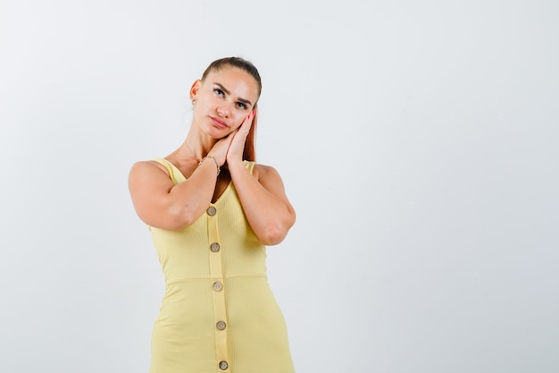 Jeune femme appuyée sur les paumes comme oreiller en robe jaune et à la pensif, vue de face.