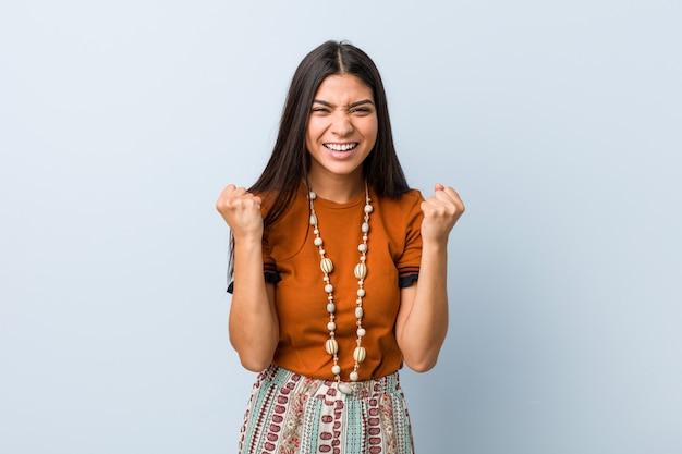 Jeune femme arabe acclamant insouciante et excitée. concept de victoire.