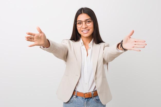 Jeune femme arabe d'affaires isolé contre un mur blanc se sent confiant donnant un câlin