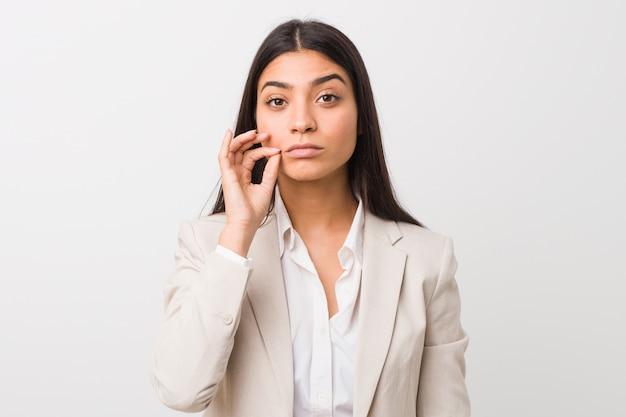 Jeune femme arabe d'affaires isolée contre un blanc avec les doigts sur les lèvres gardant un secret.
