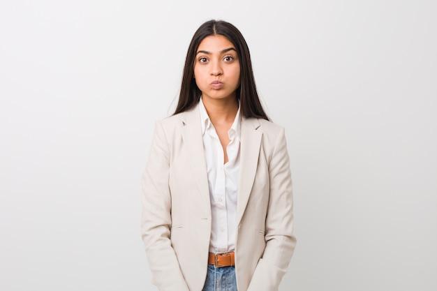 Jeune femme arabe d'affaires isolée sur un fond blanc souffle les joues, a une expression fatiguée.