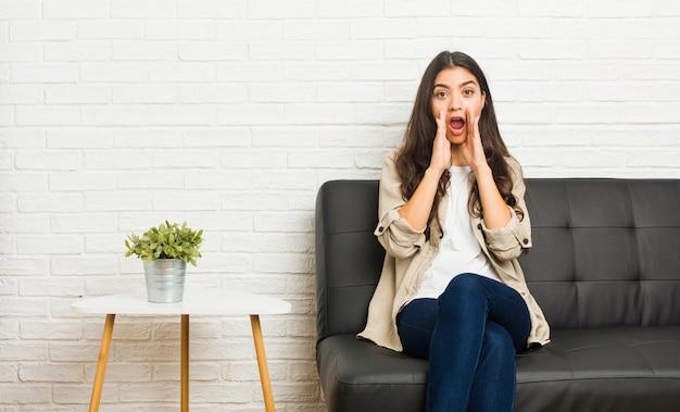 Jeune femme arabe assise sur le canapé en criant excité.