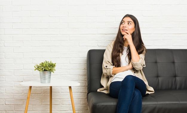 Jeune femme arabe assise sur le canapé détendue pensant à quelque chose en regardant un espace de copie.