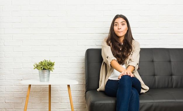 Jeune femme arabe assise sur le canapé hausse les épaules et ouvre grand les yeux confus
